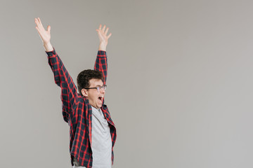 Man raising his hands up, in glasses,  checkered shirt,  gray background, isolated, positive facial emotion,  copy space