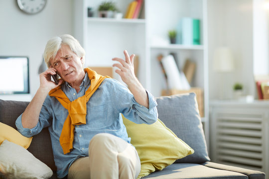 Portrait of frowning senior man speaking by phone arguing with somebody, copy space