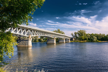 Steel bridge across the river Elbe in the town of Litomerice in the Czech Republic. Bridge in summer sunny day. Metal construction of arched bridge with pillars over the river. Architectural monument