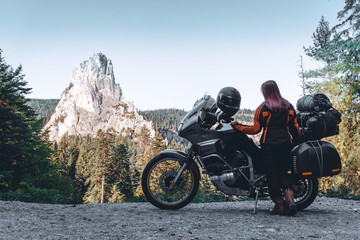 Woman biker and adveture motorcycle on mountain road in Bicaz Canyon, Romania. Travel concept, extreme, vacation in Europe, motorcyclist way, tourism, Cheile Bicazului, Europe. copy space Fototapete