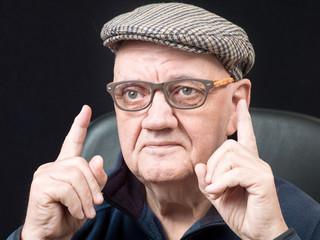 Portrait vieil homme avec lunettes et béret sur fond noir