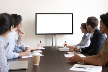 Business people group sitting at conference table looking at screen