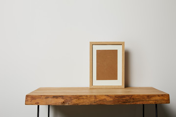 blank square frame on wooden textured table at home