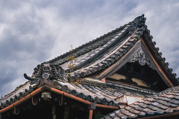 Traditional Japanese Roof detail with overgrown vegetation and specific ornaments of a traditional Japanese Shrine complex in Gion District, Kyoto, Japan.