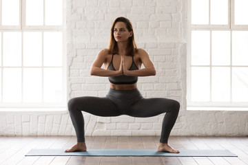 Attractive young woman practicing yoga, standing in Sumo Squat, Goddess