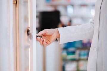 Pharmacist taking medication from a shelf, close-up.
