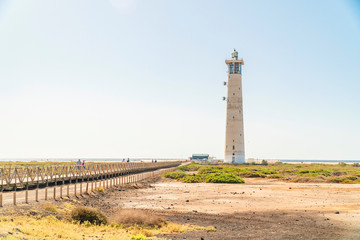 Lighthouse and wooden bridge with tourists in Morro Jable, Fuerteventura, Spain
