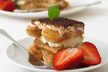 Tiramisu, homemade sweet Italian no bake dessert cheesecake, cut of cake on small plate embellished with fresh mint and a few real strawberries, on white table. Closeup.