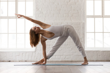 Woman practicing yoga, standing Utthita Trikonasana pose, extended triangle