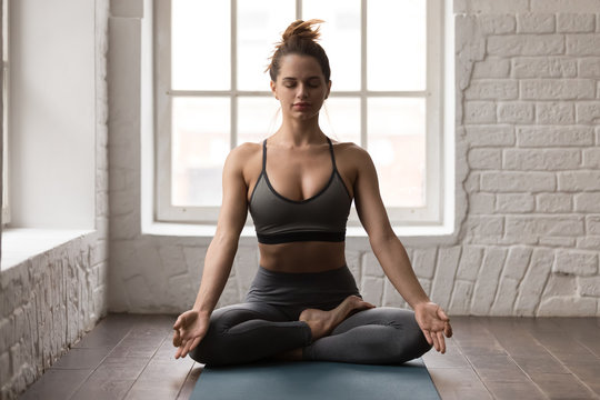 Calm woman practicing yoga, sitting in Padmasana pose, Lotus exercise