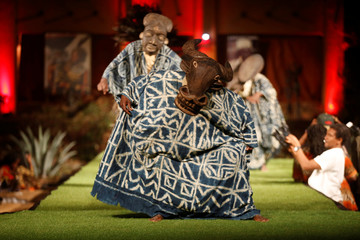 Models wearing traditional masks walk on a catwalk during a fashion show at the African Heritage House in Nairobi