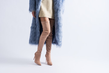 Woman in short dress, luxury pink high-heeled suede boots and blue fur coat. White background and copy space.
