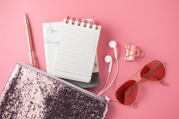 Fashion glitter bag with note pad, sunglasses, earphone and pen on pink background