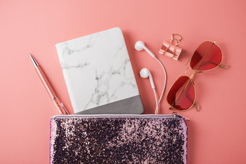 Fashion glitter bag with marble notebook, earphone, sunglasses and pen on coral pink background