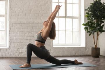 Beautiful woman practicing yoga, standing in anjaneyasana pose, Horse rider