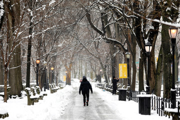 A woman walks in Riverside Park during a snow storm in upper Manhattan in New York City