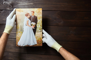 Photo of a wedding couple printed on canvas. Male hands in white gloves hold a photography with gallery wrapping on stretcher bar