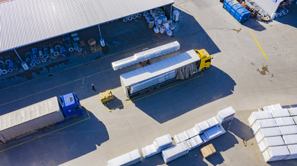 Forklift is putting cargo from warehouse to truck outdoors. Aerial. top view