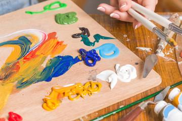 artist mixes oil acrylic paint on the palette