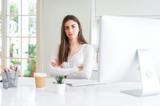 Beautiful young woman working using computer skeptic and nervous, disapproving expression on face with crossed arms. Negative person.