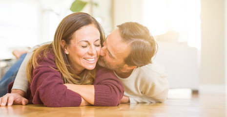 Beautiful romantic couple sitting together on the floor kissing in love at home