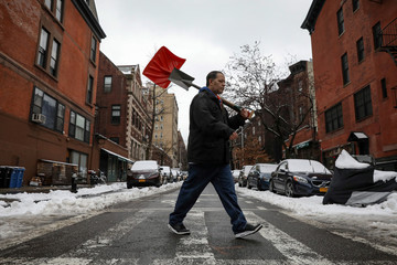 A man carries shovels during the morning commute following a winter snow storm in New York