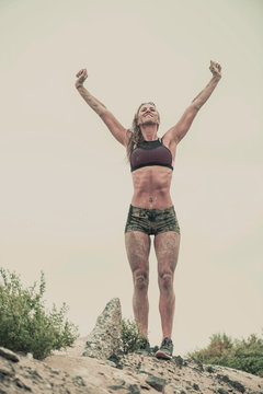 Strong athletic woman with mud on her face and body after running in rain or extreme sport celebrates with a big smile and hands raised over her head
