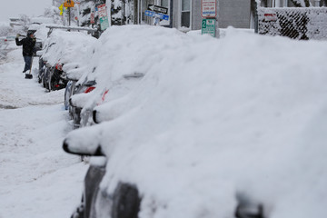 A driver shovels out his car following a winter snow storm in Somerville