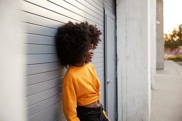 Young black woman with afro leaning in the street against grey security shutters, side view
