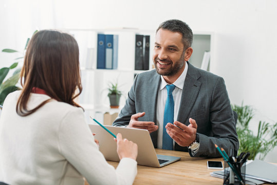 selective focus of advisor sitting at table with laptop and woman in office