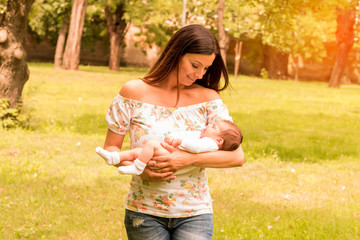 A young mother standing in the park and holding her baby