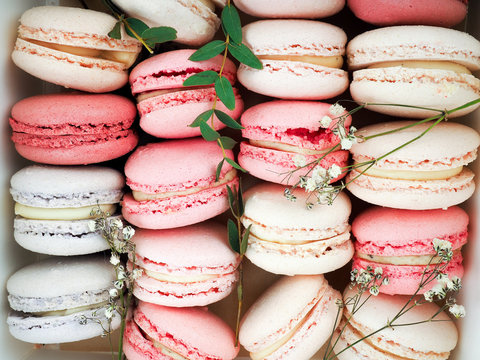 Colorful French or Italian macarons stack on white wood table with copy space for background. Dessert for served with afternoon tea or coffee break.