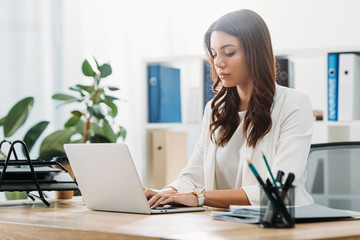 attractive businesswoman sitting at table with laptop and typing in office