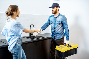 Handy man having a deal with young woman client after the repairment on the kitchen. Home repair service concept