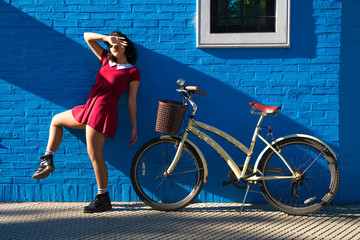 A woman with a bike posing in front of a brick wall