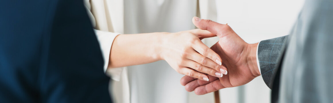 selective focus of man and woman shaking hands at office