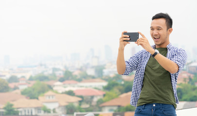 attractive and Charming man using digital smartphone technology to take photography in the city outdoor. asian handsome man in casual. Happy travel guy smiling outdoor