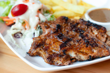 Chicken steak is a fast food, chicken steak this dish consists of with salad which has purple lettuce carrot tomato salad dressing french fries and black pepper sauce all in a white plate.