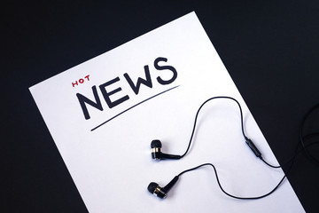 """Hot news concept.  White paper with hand lettering text """"Hot News"""" and headphones."""
