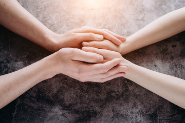 Close up view of couple holding hands, loving caring man supporting woman, giving psychological support, help or protection, understanding in marriage relationships