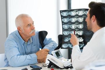 senior doctor explaining xray to patient