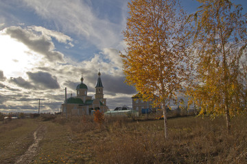 autumn landscape with clouds over the village church in Russia