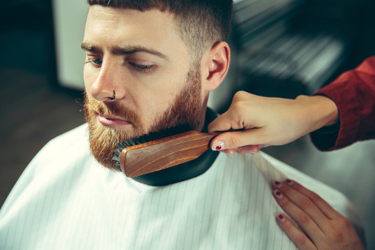 Client during beard shaving in barbershop. Female barber at salon. Gender equality. Woman in the male profession. Hands close up