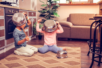 Relaxed kids playing at home with kitchenware