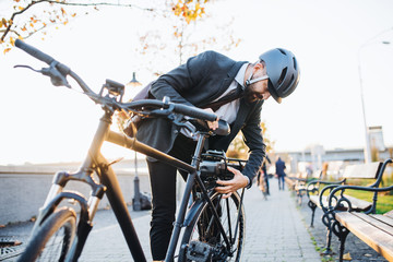 Hipster businessman commuter setting up electric bicycle in city. Fototapete