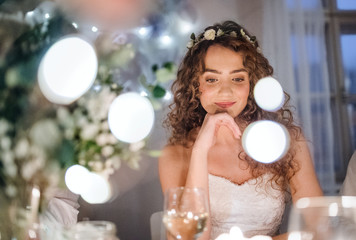 A front view of a young bride sitting at a table on a wedding.