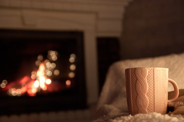 a cup of hot tea on the background of the fireplace, soft and fluffy rug, warm and cozy atmosphere
