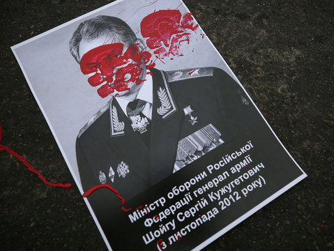 Paint is splashed onto a poster depicting Russian Defence Minister Shoigu during a rally to commemorate the fourth anniversary of the battle in the eastern city of Ilovaisk, in front of the Russian Embassy in Kiev