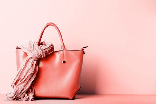 Female handbag with scarf on living coral background