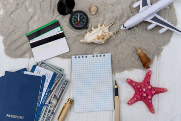 Travelling plan with notepad and toy plane on sand